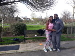 A couple pose during a workout in the park