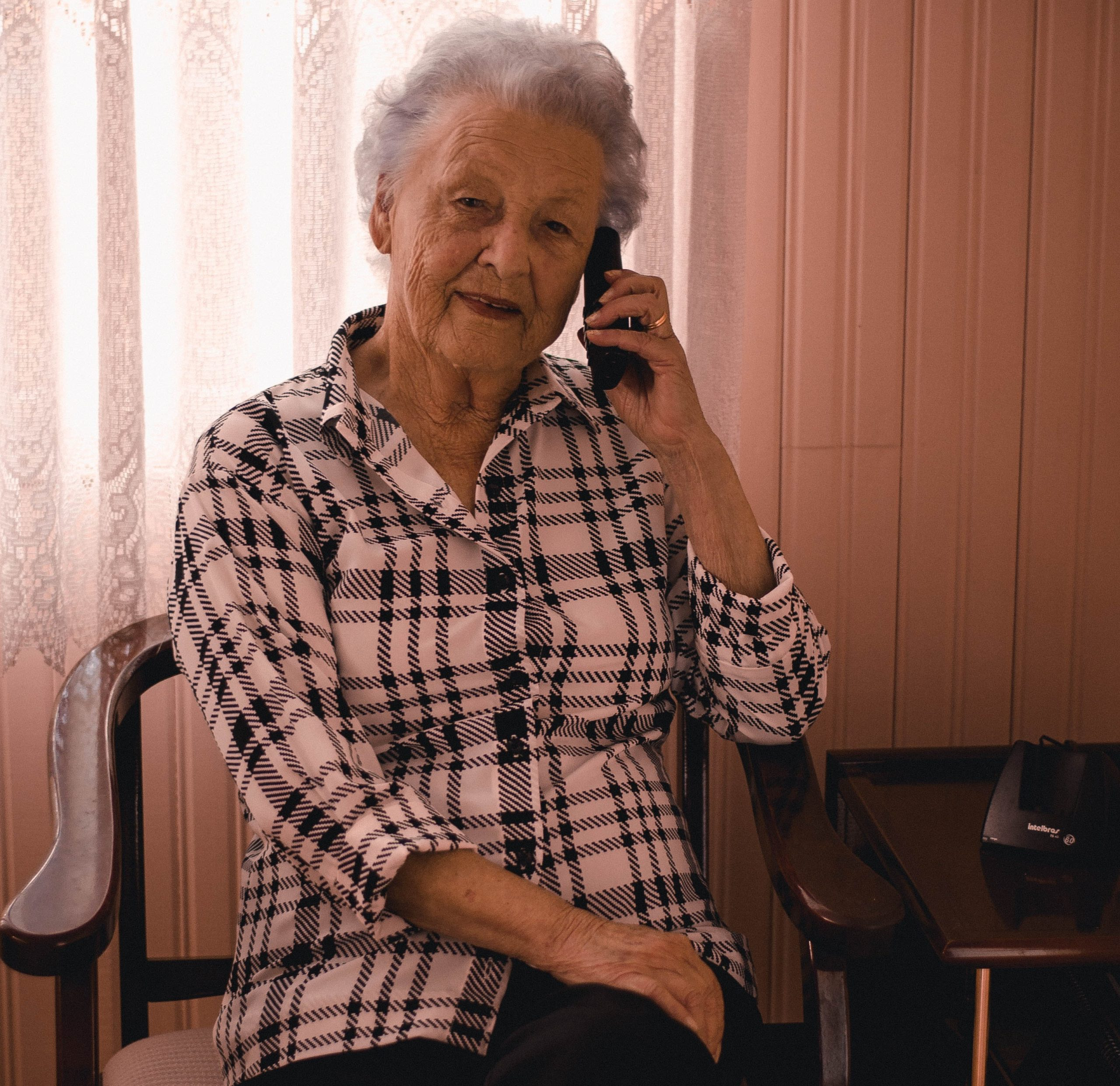 An elderly woman answering the phone